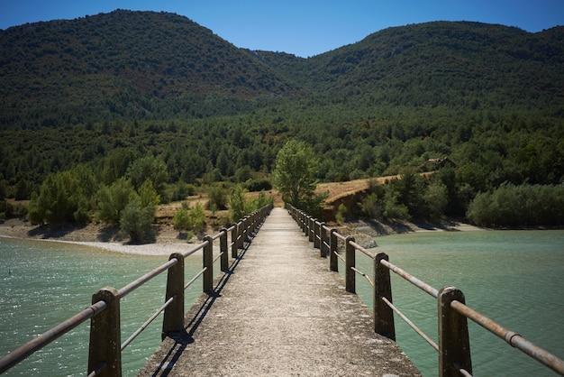 Konkrete fußgängerbrücke auf einer bucht zwischen grünen hügeln Kostenlose Fotos