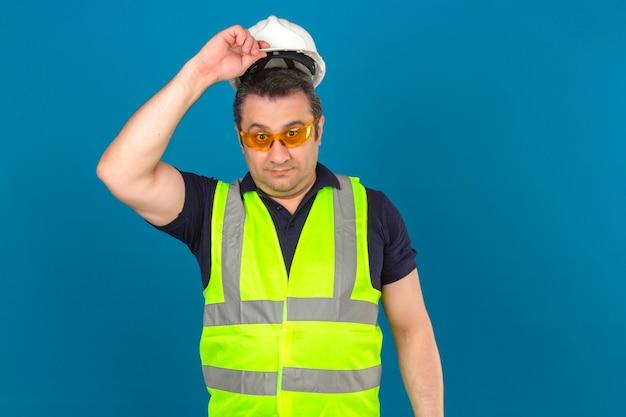 Konstrukteur mann mittleren alters, der gelbe weste der konstruktion und sicherheitshelm trägt, der überrascht sieht, helm über isolierter blauer wand abzunehmen Kostenlose Fotos