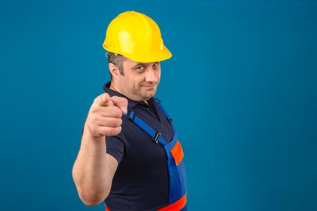 Konstrukteur mittleren alters, der bauuniform und sicherheitshelm trägt, der glücklich lächelt und seine zeigefinger auf kamera über isolierte blaue wand zeigt Kostenlose Fotos