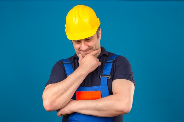 Konstrukteur mittleren alters, der konstruktionsuniform und sicherheitshelm trägt, der kinn berührt und über isolierte blaue wand denkt Kostenlose Fotos