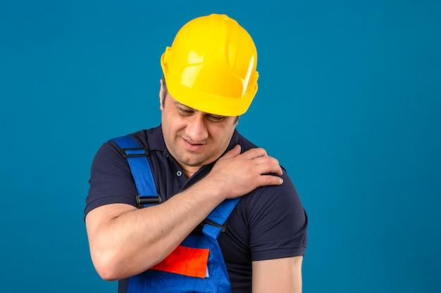 Konstrukteur mittleren altersmann, der konstruktionsuniform und sicherheitshelm trägt, der schulter berührt, die schmerzen über isolierter blauer wand hat Kostenlose Fotos