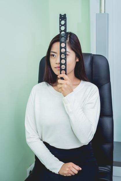 Konsultation mit einem augenarzt. junge asiatische frau im klinikbüro. Premium Fotos