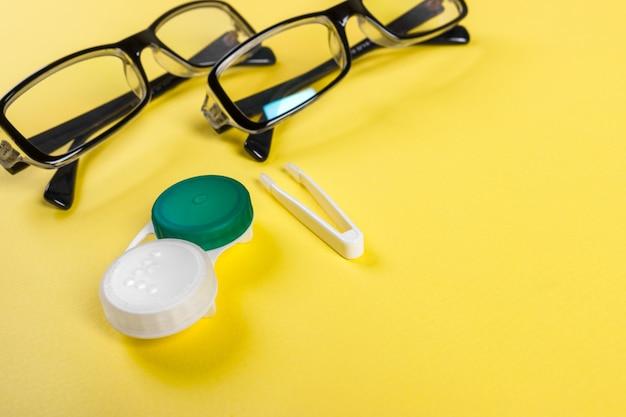 Kontaktlinsen stellten mit plastikkasten und pinzette mit gläsern auf dem hintergrundplan auf einem lila hintergrund ein Premium Fotos