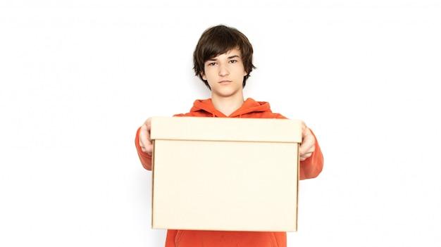 Kontaktlose lieferung. mann in einer medizinischen maske und handschuhen hält eine box. Premium Fotos