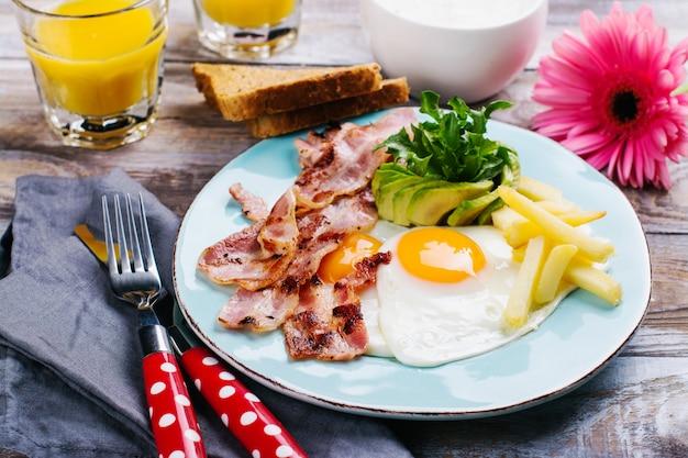 Kontinentales frühstück mit spiegeleiern, speck und getränken Premium Fotos