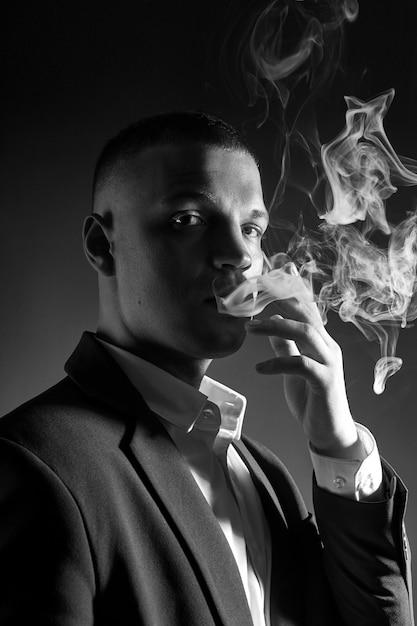 Kontrastporträt eines rauchenden manngeschäftsmannes in einem teuren anzug Premium Fotos
