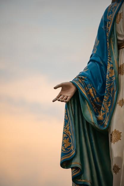 Konzentrieren sie sich auf die hand der seligen jungfrau maria, mutter von jesus am blauen himmel Premium Fotos