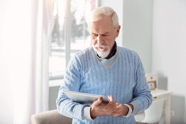 Konzentriert sich auf das lesen. schöner älterer bärtiger mann, der eine tafel hält und davon liest, völlig in das buch eingetaucht Premium Fotos