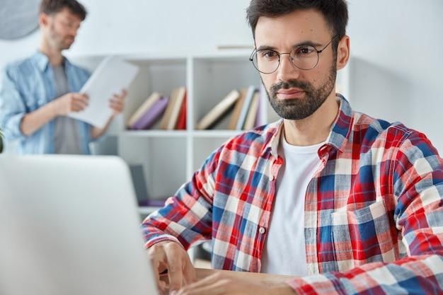 Konzentrierte freiberufler arbeiten fern am laptop, haben stoppeln und tragen eine brille Kostenlose Fotos