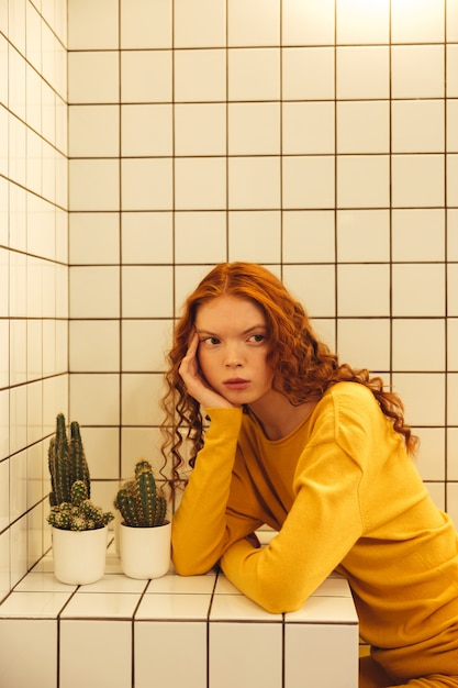 Konzentrierte junge rothaarige lockige dame, die im café sitzt Kostenlose Fotos