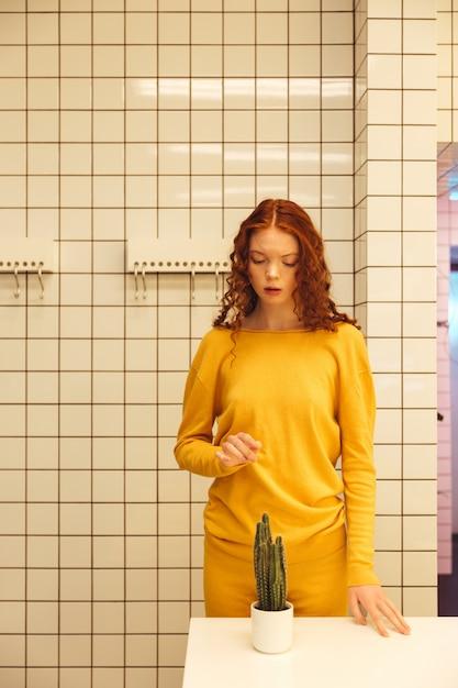 Konzentrierte junge rothaarige lockige dame, die im café steht Kostenlose Fotos