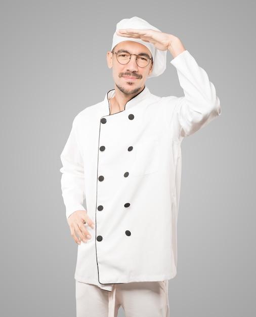 Konzentrierter junger koch mit einer geste des wegschauens Premium Fotos