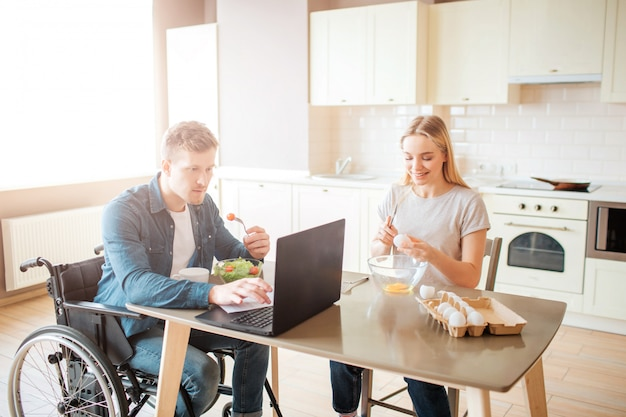 Konzentrierter junger mann auf rollstuhl, der mit laptop arbeitet und salat isst. studieren mit behinderung und inklusivität. mann mit besonderen bedürfnissen. junge frau sitzt daneben und kocht. eier brechen. Premium Fotos