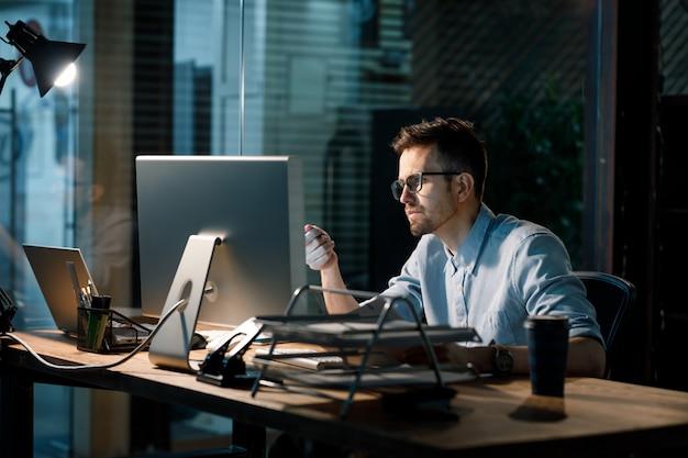 Konzentrierter mann, der spät mit computer arbeitet Premium Fotos