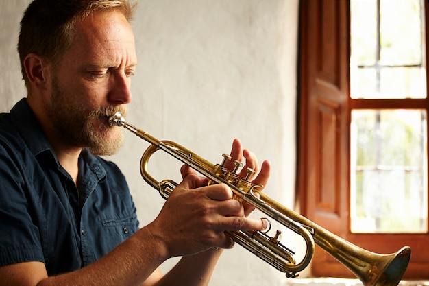 Konzentrierter musiker, der sein instrument spielt Kostenlose Fotos