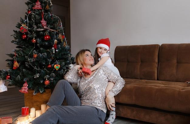 Konzept der familie, weihnachten, feiertage und der menschenglücklichen mutter und der kleinen tochter, die zu hause auf der couch sitzen Premium Fotos