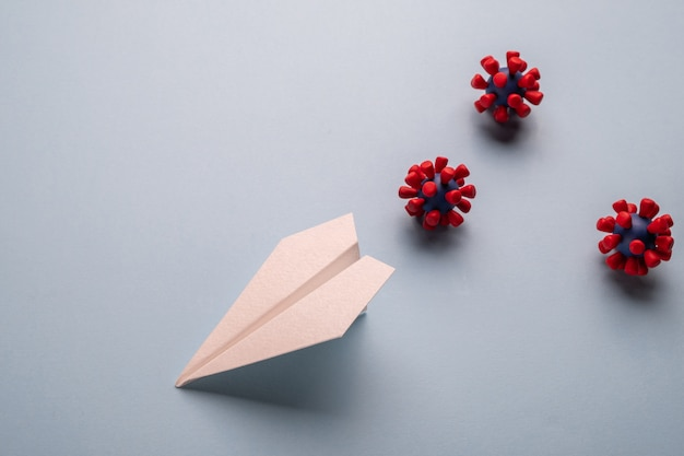 Konzept der fliegengefahr. papierebene und modelle des covid-19-virus Premium Fotos