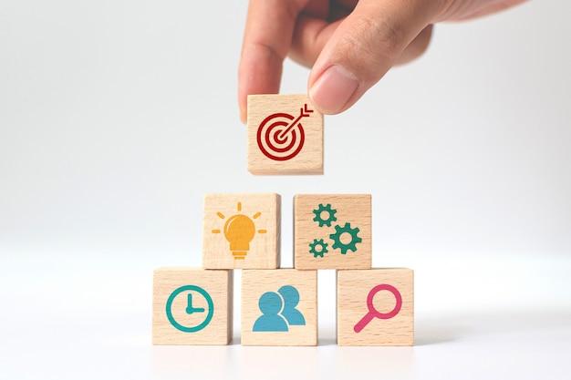 Konzept der geschäftsstrategie und des aktionsplans. hand setzen holzwürfelblock stapeln mit symbol Premium Fotos