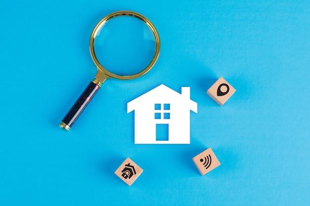 Konzept der immobilie mit lupe, holzklötzen, papierhausikone auf blauem tisch flach legen. Kostenlose Fotos