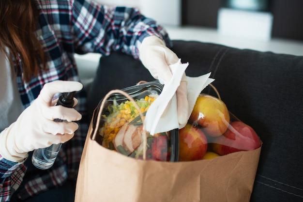 Konzept der lebensmittellieferung. ein junges mädchen in handschuhen verarbeitet antiseptische produkte. sie kam aus dem supermarkt und brachte viel essen in säcken. Premium Fotos