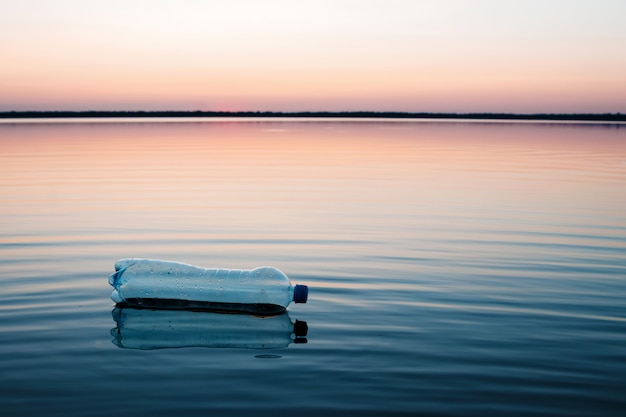 Konzept der verschmutzung, kreativ. eine plastikflasche, die in den ozean schwimmt Premium Fotos