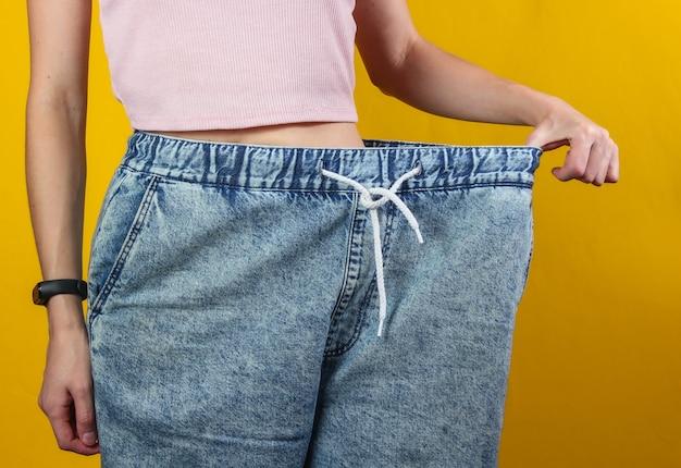 Konzept des abnehmens. frau in sehr großen jeans auf gelbem studiohintergrund. foto zuschneiden Premium Fotos