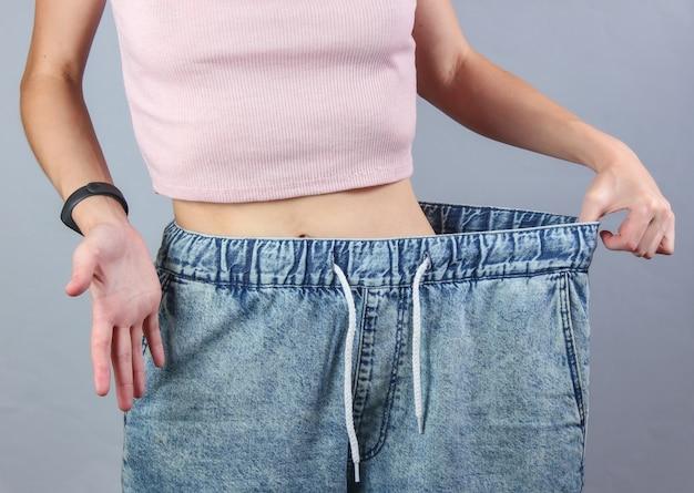 Konzept des abnehmens. frau in sehr großen jeans auf grauem studiohintergrund. Premium Fotos