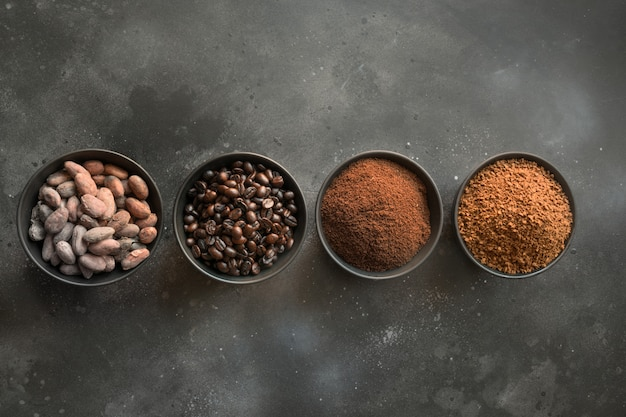 Konzept des kakaos und der kaffeebohnen in den schüsseln auf dunkelheit. Premium Fotos