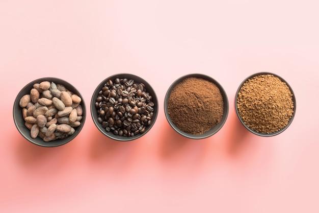 Konzept des kakaos und der kaffeebohnen in den schüsseln auf rosa hintergrund. Premium Fotos