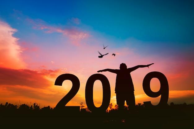 Konzept des neuen jahres 2019, schattenbild der glücklichen frau haben freiheit und freudige mit den vögeln, die auf himmel fliegen Premium Fotos