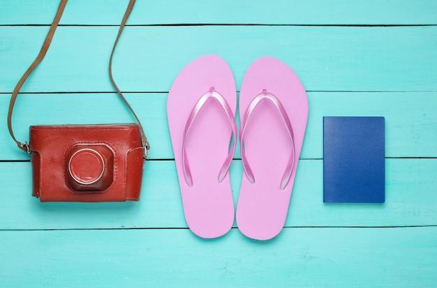 Konzept des urlaubs am strand, tourismus. sommerreisender hintergrund. flip flops, retro-kamera, pass auf blauem holzhintergrund. Premium Fotos