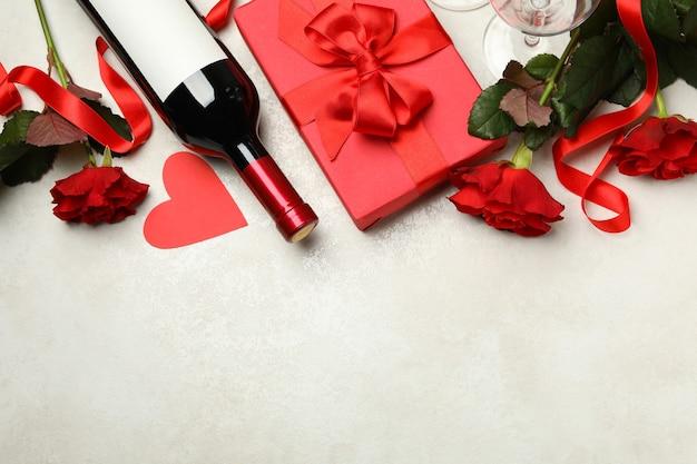 Konzept des valentinstags mit rosen, wein und geschenkbox auf weißem strukturiertem hintergrund Premium Fotos