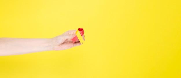 Konzept des welthepatitis-tages. frau hält in ihrer hand bewusstseinssymbol rot-gelbes band. gelber hintergrund. speicherplatz kopieren Premium Fotos