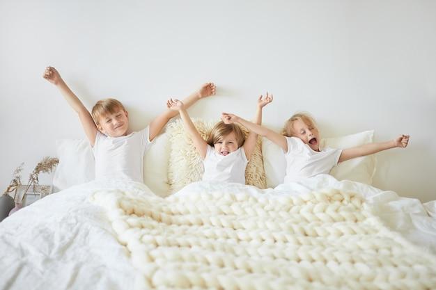 Konzept für bettwäsche, schlaf, ruhe und entspannung. innenaufnahme von drei kindern, die sich schläfrig fühlen, während sie am frühen morgen vor der schule aufwachen. zwei brüder und schwestern gähnen und strecken sich im bett Kostenlose Fotos