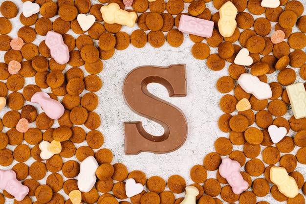 Konzept für die kinderparty in saint nicolas tag fünf dezember. pepernoten, schokoladenbuchstaben, süßigkeiten und karotten für pferde. holländischer feiertag sinterklaas. Premium Fotos