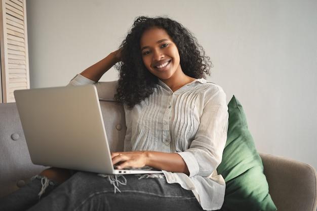 Konzept für menschen, freizeit, modernen lebensstil, technologie und elektronische geräte. attraktive glückliche junge gemischte rassenfrau, die online-kommunikation genießt, video-chat mit laptop-computer zu hause hat Kostenlose Fotos
