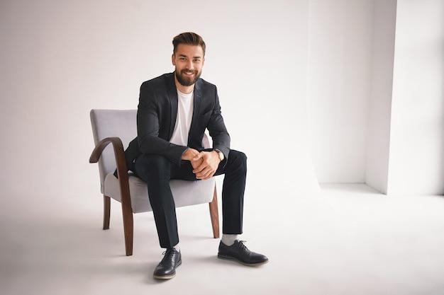 Konzept für menschen, lifestyle, business, stil, mode und herrenbekleidung. positiver erfolgreicher junger ceo, der im sessel sitzt, lächelt, gekleidet in eleganten schuhen, hosen, jacke und weißem t-shirt Kostenlose Fotos