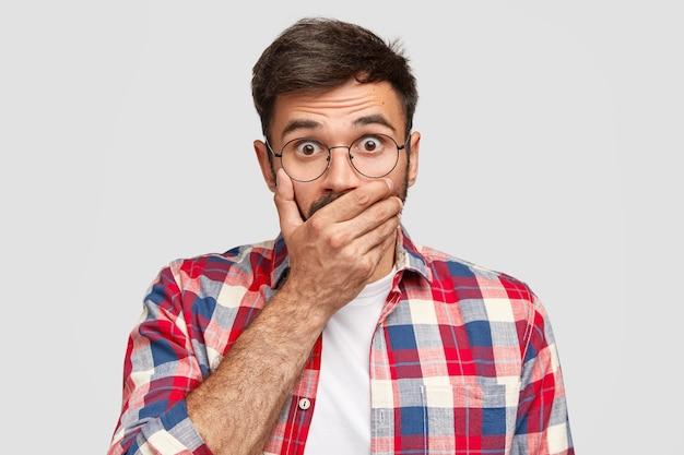 Konzept für menschen, reaktionen, emotionen und mimik. der verängstigte europäer bedeckt den mund und starrt vor angst Kostenlose Fotos