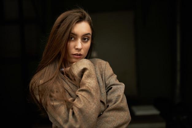 Konzept für stil, mode, schönheit und weiblichkeit. entzückende wunderschöne junge frau mit losen braunen haaren, die kamera mit ernstem selbstbewusstem gesichtsausdruck betrachten, gekleidet in übergroße jacke oder mantel Kostenlose Fotos