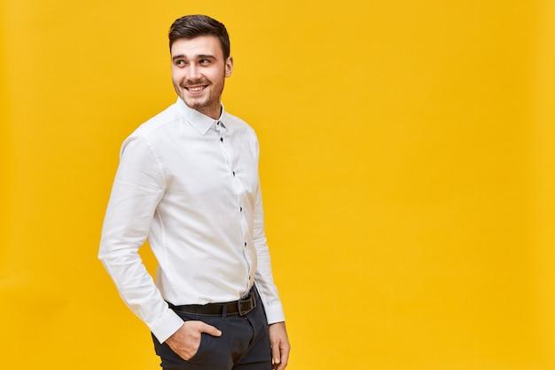 Konzept für stil, mode und herrenbekleidung. schöner positiver junger geschäftsmann, der isoliert mit hand in der tasche der stilvollen schwarzen jeans aufwirft, zurückblickend, mit fröhlichem gesichtsausdruck habend Kostenlose Fotos