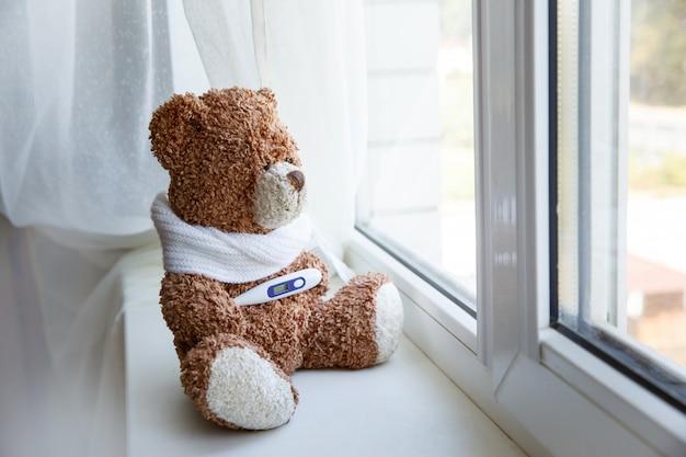 Konzept teddybär kinderkrankheiten auf weißem hintergrund. teddy bear, der alleine auf weißem fenster sitzt Premium Fotos