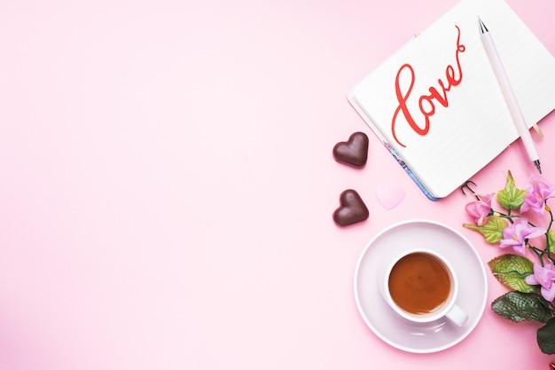 Konzept valentinstag. pralinen und kaffee, herzen auf einem rosa hintergrund. flacher laienkopienraum. grußkarte und geschenk. Premium Fotos