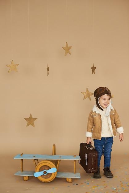 Konzept von träumen und reisen. pilot flieger kind mit einem spielzeugflugzeug und koffer spielt in einer beige Premium Fotos