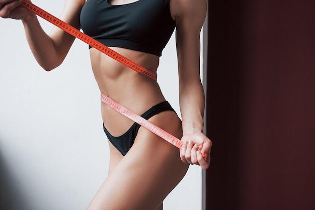 Konzeption der gesundheitsfürsorge. nahaufnahme des schlanken körpers der fitness des jungen mädchens, der durch das band misst Kostenlose Fotos