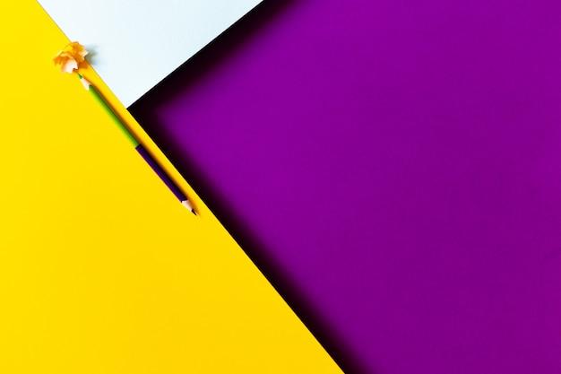Konzeptioneller minimalistischer papierhintergrund mit zweifarbigem bleistift und schnitzeln vom schärfen. zurück zu schule und bildungskonzept. Premium Fotos