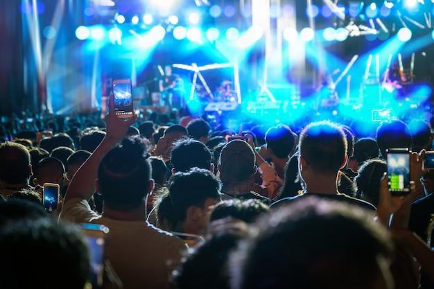Konzertmenge der musikfanclubhand, die das intelligente mobiltelefon hält, das videoaufzeichnung oder live nimmt Premium Fotos