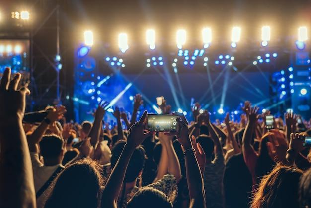 Konzertmenge der musikfanclubhand unter verwendung des mobiltelefons, das videoaufzeichnung oder livestream nimmt Premium Fotos