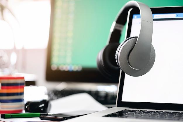Kopfhörer hängen am laptopmonitor mit leerem bildschirm. Premium Fotos