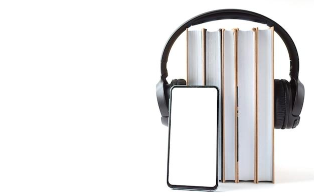 Kopfhörer, telefon und bücher auf weißem hintergrund. hörbuchkonzept. Premium Fotos