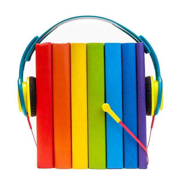 Kopfhörer um regenbogen-mehrfarbenbücher lokalisiert auf einem weißen hörbuchkonzept Premium Fotos